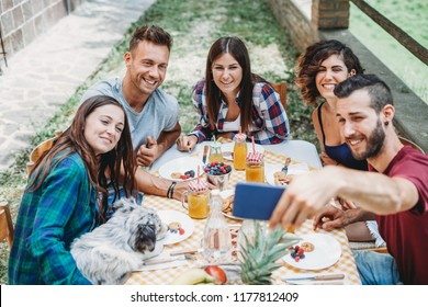 Group of young friends takes a selfie with smartphone during breakfast in the countryside. On the table fruit, tart and biscuits. A dog eats from a plate while the millennials are distracted