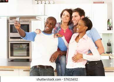Group Of Young Friends Taking Photo In Modern Kitchen
