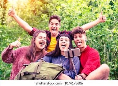 Group of young friends taking selfie with stick on  green forest background - Teenagers having fun using mobile phone technology for self photo on camping excursion day - Soft vintage filter look