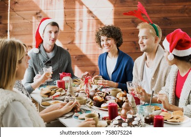 Group of young friends talking by festive table while having tea with homemade pastry