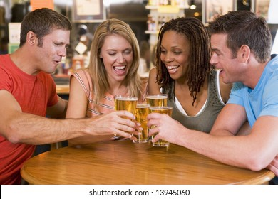 Group of young friends toasting in a bar