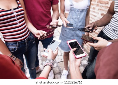 group of young friends using cell phones side view close up on hands with smartphones. concept of millennials addiction to cell phone and gadgets an digital communication technology