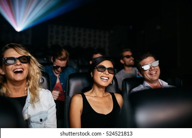 Group of young friends watching 3d movie in theater and laughing. Young men and women wearing 3d glasses in cinema hall.