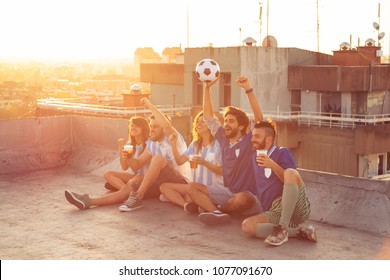 Group of young friends watching a football match on a building rooftop, cheering and drinking beer. Focus on the guys on the right