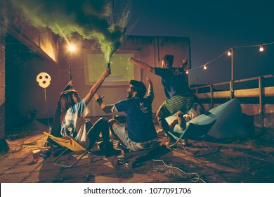Group of young friends watching a football match on a building rooftop; girl holding a smoke bomb after her team scored a goal, celebrating