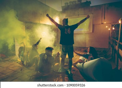Group of young friends watching a football match on a building rooftop; girl holding a smoke bomb after her team scored a goal, celebrating. Focus on the men in the middle