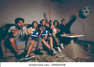 Group of young friends watching a football match on a building rooftop, cheering eating pizza and drinking beer, cheerful after they scored a goal