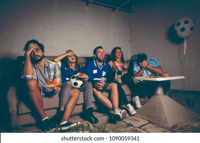 Group of young friends watching a football match on a building rooftop, cheering eating pizza and drinking beer, disappointed after they lost the match