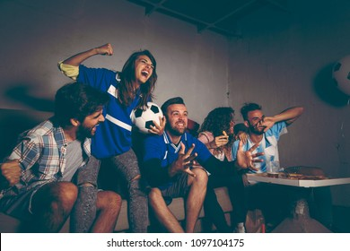 Group of young friends watching a football match on a building rooftop, celebrating after their team has scored a goal