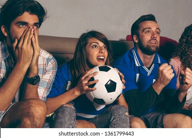 Group of young friends watching a football match on a building rooftop, cheering and yelling, excited about the game