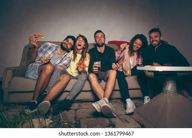 Group of young friends watching a movie on a building rooftop terrace, eating pizza, drinking beer and having fun