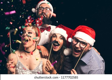 Group of young friends wearing Santa hats having fun at New Year's Eve Party, posing for photos with masks