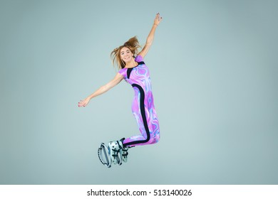 The group of young girls, jumping on kangoo training on gray