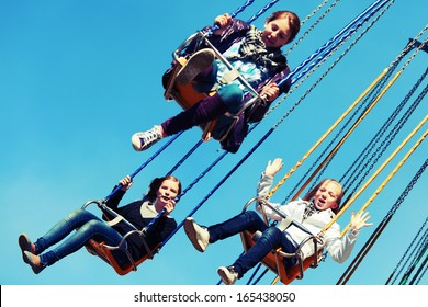 Group of young girls on the chain swing carousel