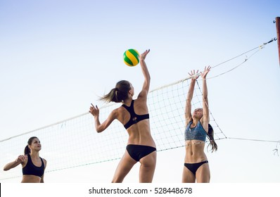 Group of young girls playing beach volleyball during sunset or sunrise
