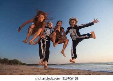Group young girls in scary skeleton and wild savage costumes jumping high in air with fun before Halloween night party on sunset sea beach. Active people, lifestyles and event celebrations on holidays