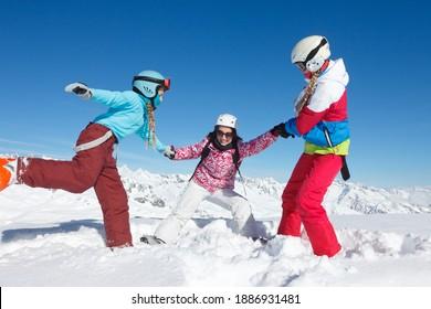 Groupe de jeunes filles et d'adolescents en vacances d'hiver dans les montagnes jouant dans la neige sur les pistes de ski qui débordent d'énergie