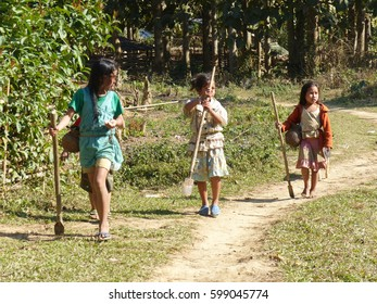 Group of young girls walking through the forest going back home in Laos. January 2015.