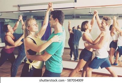Group of young glad people learning salsa at dance class. Focus on brunet man