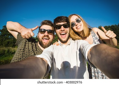 A group of young good looking multiethnic hipster friends do selfie photo portrait in the park while summer sunset