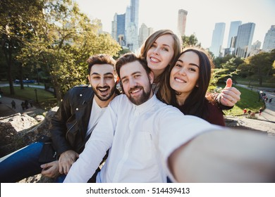 A group of young good looking multiethnic hipster friends taking selfie self-portrait in Central Park, New York. Mixed race students have fun and take photo for travel blog.