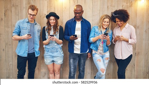 Group of young good looking people standing together over wooden wall background all staring into their smartphones