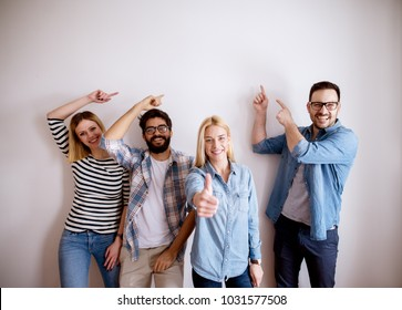 Group of young handsome colleague people standing against the wall showing at empty editable space above while one girl standing with thumb up and looking at the camera.