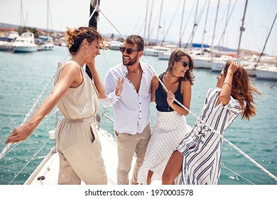 A group of young handsome models is standing on the bow of the yacht and having a good time while riding through the dock on a beautiful summer day on the seaside. Summer, sea, vacation, friendship