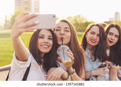 Group of young happy carefree girls friends making selfie on summer city street, sunset time background
