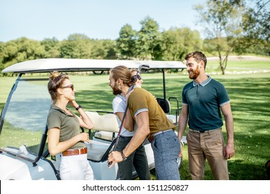 Group of a young happy friends gathering together before the golf game near the car on a playing course on a sunny day