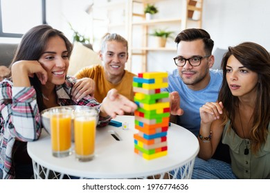 Group of young happy friends having fun playing wood board game