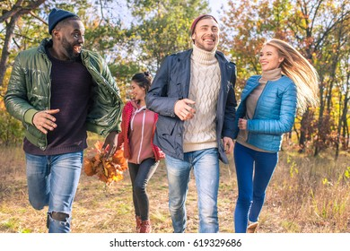 Group of young happy friends walking in autumn park and collecting colorful leaves