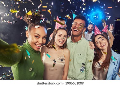 Group of young happy multiracial people wearing birthday hats making a selfie on mobile phone, confetti falling in the air