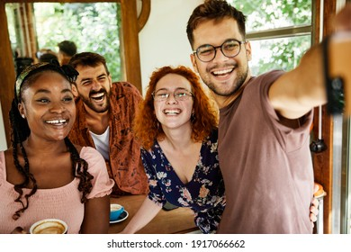 Group of young happy people friend having fun and taking selfie  in a coffee shop