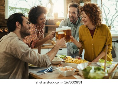 Group of young happy people having fun while toasting with beer during lunch in dining room.