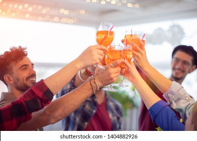 Group of young happy people toasting with glasses of spritz (cocktails) - rooftop birthday party with best friends concept