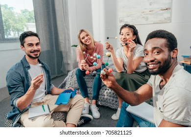 group of young happy students studying at home and looking at camera