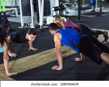 group of young healthy people doing pushups at a  gym