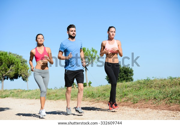 group of young healthy people running outdoor and doing fitness exercises in summer