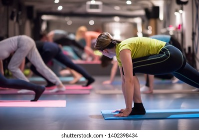 group of young healthy sporty women working out with instructor doing aerobics exercises in a fitness studio fitness, sport, training, gym and lifestyle concept