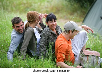 Group of young hikers sitting in the grass