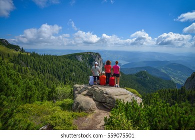 Group of young hikers sitting on a cliff edge in the Ceahlau mountains in Romania