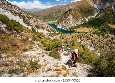 Group of young hikers trekking in mountains. Two women two men backpacking in summer near Sary Chelek lake, Sary-Chelek Jalal Abad region, Kyrgyzstan, Trekking in Central Asia.