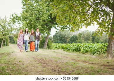 Group of young hippies walking on a natural path