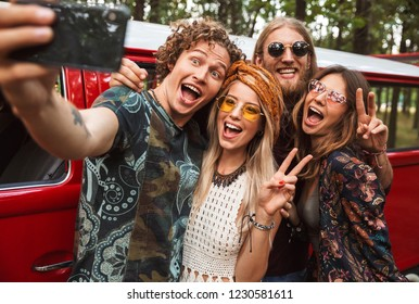 Group of young hippy men and women smiling and taking selfie on mobile phone near vintage minivan into the nature