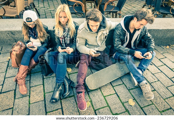 Group of young hipster friends using smart phone with disinterest on each other - Modern situation of technology addiction in alienated lifestyle - Internet wifi connection on vintage filtered look