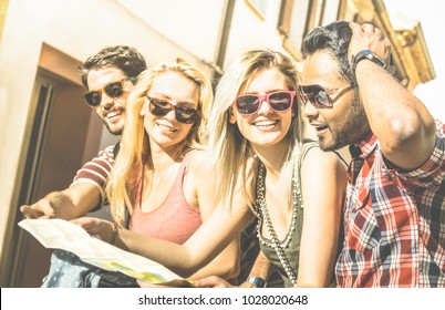 Group of young hipster tourists friends cheering with city map in the old town - Travel lifestyle concept with happy people having fun together - Warm bright afternoon filter with strong sunshine tone