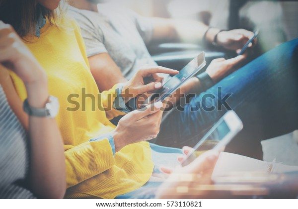 Group of young hipsters sitting on sofa holding en hands and using digital tablet,smartphone.Coworking team concept.Horizontal,blurred background