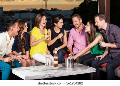 Group of young Hispanic adults having drinks in a terrace at sunset