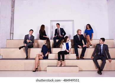 Group of a young international man and woman successful business workers are speaking among themselves. Men and women in formal wear prosperous entrepreneurs having meeting in an informal atmosphere